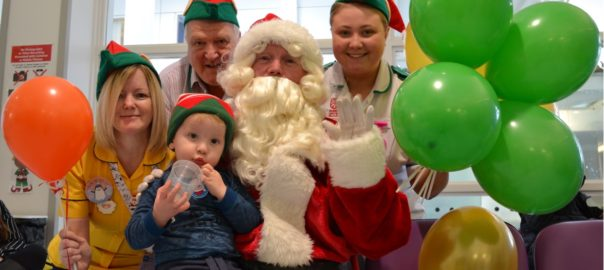 Santa is delighted to see young Cuan pick up his balloon and sweets, with a little help from Michael Maitland, Probation Community Services Offer, Nurse Geraldine Lavery, and Nurse Leah Kidd
